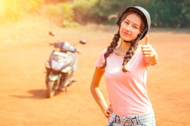 Mulher bonita e jovem em um capacete de segurança fica na frente de uma motocicleta (bicicleta) e mostra o dedo polegar para cima. conceito de direção segura de scooter