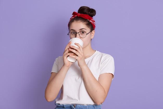 Mulher bonita e jovem feliz com uma faixa vermelha e uma camiseta casual branca, posa contra o espaço lilás, bebendo café em um copo de papel