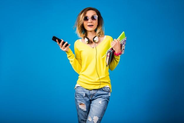 Mulher bonita e jovem hippie segurando livros e olhando para o smartphone