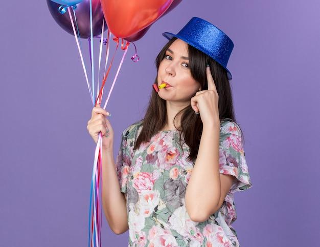 Mulher bonita e jovem impressionada com um chapéu de festa segurando balões, soprando o apito de festa, colocando o dedo no templo isolado na parede azul