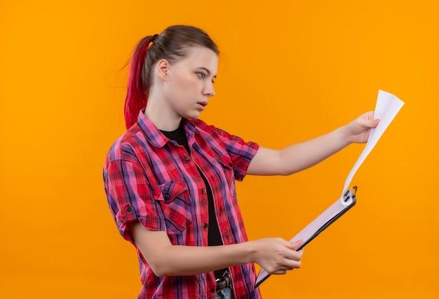 Mulher bonita e jovem impressionada de camisa vermelha folheando a prancheta na mão na parede amarela isolada