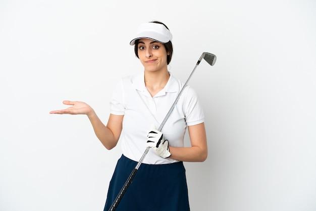 Mulher bonita e jovem jogador de golfe isolada no fundo branco, tendo dúvidas ao levantar as mãos