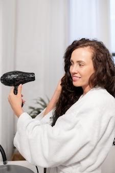 Mulher bonita e jovem sorridente com secador de cabelo cuidando de seus longos cabelos escuros ondulados após lavá-los no banheiro