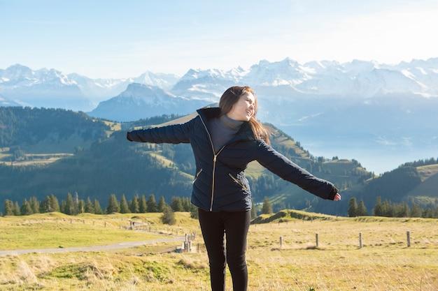 Mulher bonita é liberdade no fundo de pico de montanha de neve