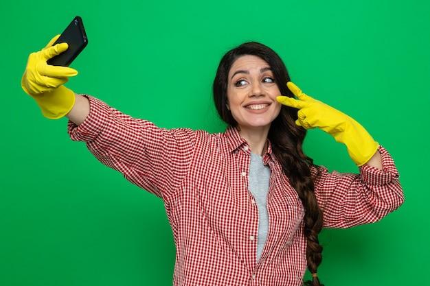 Mulher bonita e limpadora caucasiana sorridente com luvas de borracha tirando uma selfie e gesticulando sinal de vitória