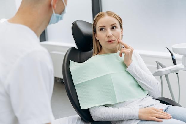 Mulher bonita e loira conta a um dentista que está com dor de dente. mulher tocando as bochechas