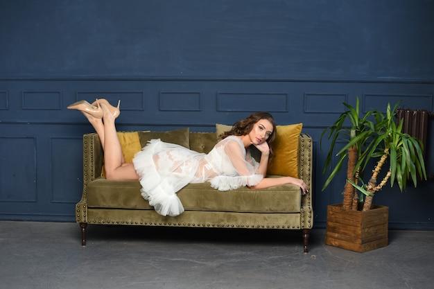 Mulher bonita e luxuosa em um roupão de renda boudoir em um interior caro, estúdio
