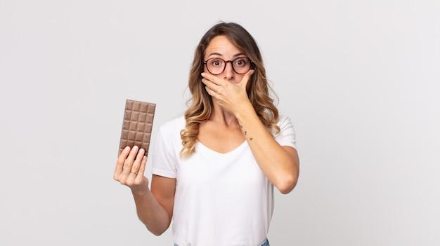 Mulher bonita e magra cobrindo a boca com as mãos em choque e segurando uma barra de chocolate