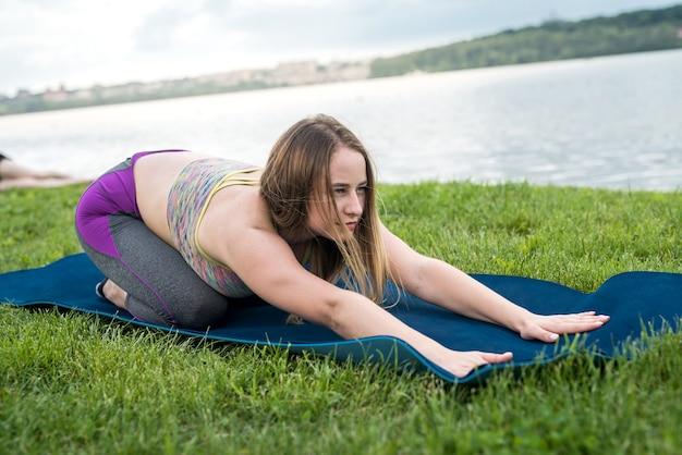 Mulher bonita e magra com roupas esportivas pratica poses de ioga na esteira ao lado de um lago em um dia ensolarado de verão, ginástica ao ar livre