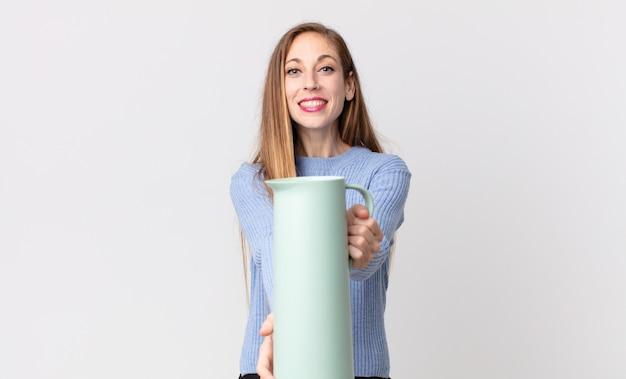Mulher bonita e magra com uma garrafa térmica de café