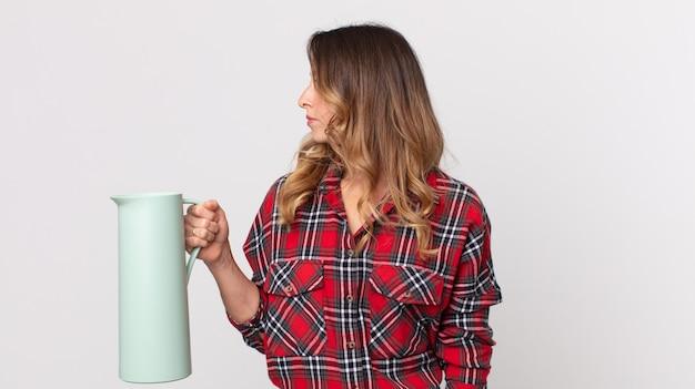 Mulher bonita e magra em vista de perfil pensando, imaginando ou sonhando acordada e segurando uma garrafa térmica de café
