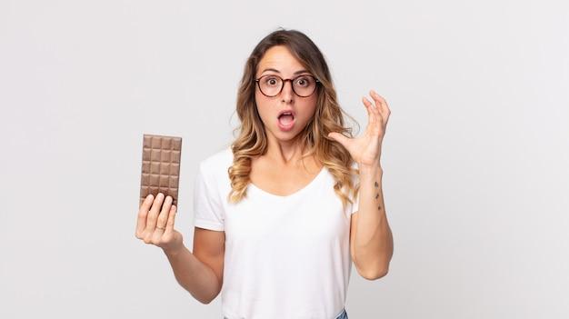 Mulher bonita e magra gritando com as mãos para o alto e segurando uma barra de chocolate
