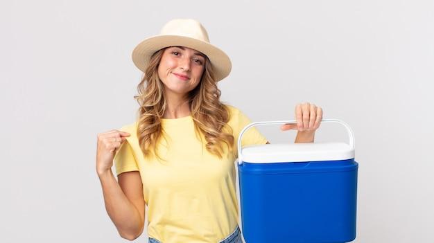 Mulher bonita e magra, parecendo arrogante, bem-sucedida, positiva e orgulhosa, segurando uma geladeira de piquenique de verão