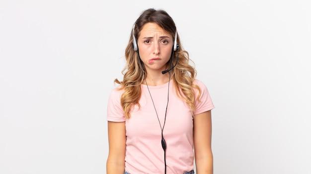 Mulher bonita e magra parecendo perplexa e confusa .assistente do operador com um fone de ouvido