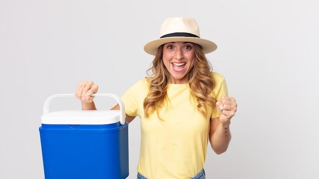 Mulher bonita e magra se sentindo chocada, rindo e comemorando o sucesso e segurando uma geladeira de piquenique de verão