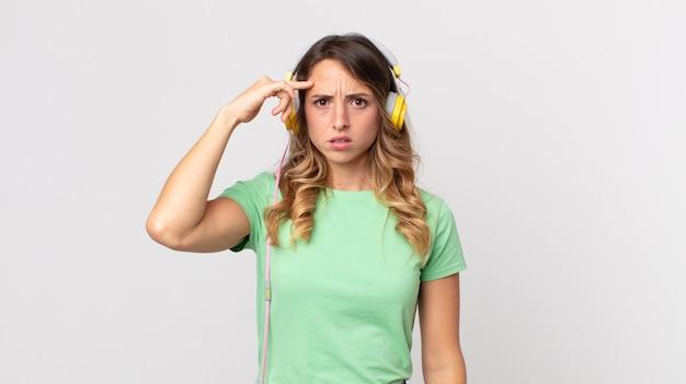 Mulher bonita e magra se sentindo confusa e intrigada, mostrando que você é louco ouvindo música com fones de ouvido
