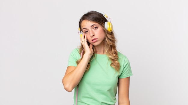 Mulher bonita e magra se sentindo entediada, frustrada e com sono depois de ouvir música cansativa com fones de ouvido