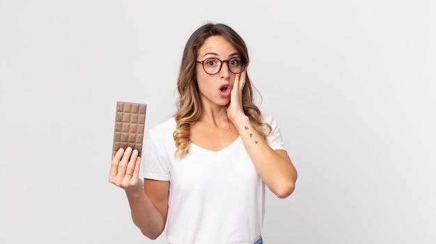 Mulher bonita e magra se sentindo feliz, animada e surpresa, segurando uma barra de chocolate