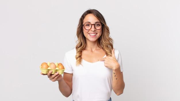 Mulher bonita e magra se sentindo feliz e apontando para si mesma com um animado e segurando uma caixa de ovos