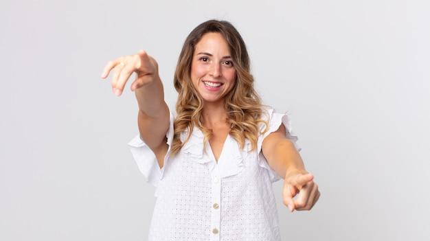 Mulher bonita e magra se sentindo feliz e confiante, apontando para a câmera com as duas mãos e rindo, escolhendo você