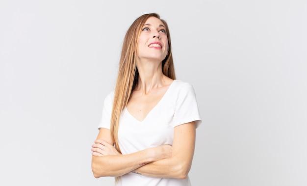 Mulher bonita e magra se sentindo feliz, orgulhosa e esperançosa, imaginando ou pensando, olhando para cima para copiar o espaço com os braços cruzados