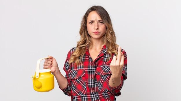 Mulher bonita e magra se sentindo irritada, irritada, rebelde e agressiva e segurando um bule de chá