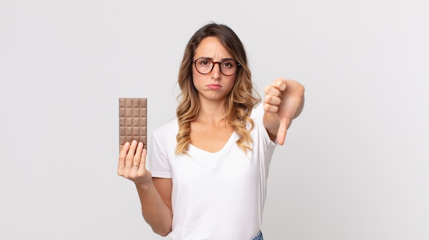 Mulher bonita e magra se sentindo mal, mostrando os polegares para baixo e segurando uma barra de chocolate