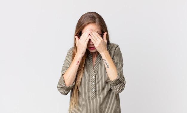 Mulher bonita e magra se sentindo triste, frustrada, nervosa e deprimida, cobrindo o rosto com as duas mãos, chorando
