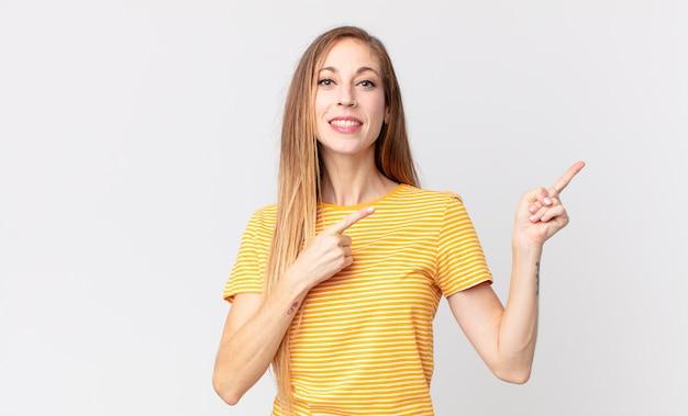 Mulher bonita e magra sorrindo alegremente e apontando para o lado e para cima com as duas mãos mostrando o objeto no espaço da cópia