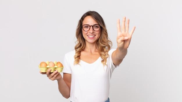 Mulher bonita e magra sorrindo e parecendo amigável, mostrando o número quatro e segurando uma caixa de ovos
