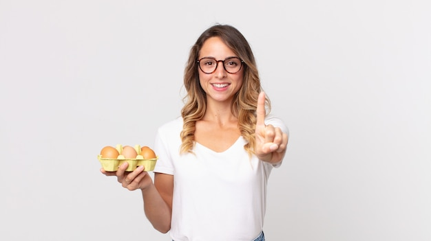 Mulher bonita e magra sorrindo e parecendo amigável, mostrando o número um e segurando uma caixa de ovos