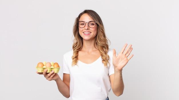 Mulher bonita e magra sorrindo feliz, acenando com a mão, dando as boas-vindas, cumprimentando você e segurando uma caixa de ovos