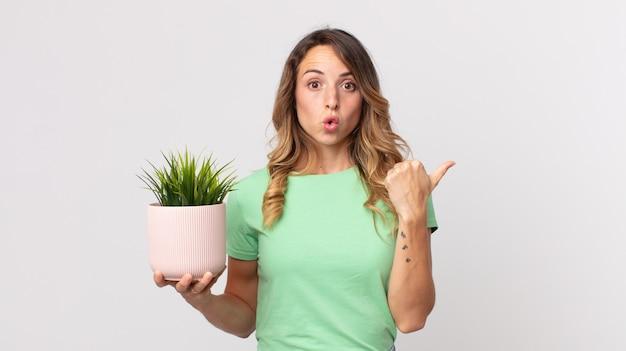 Mulher bonita e magra, surpresa e sem acreditar, segurando uma planta decorativa