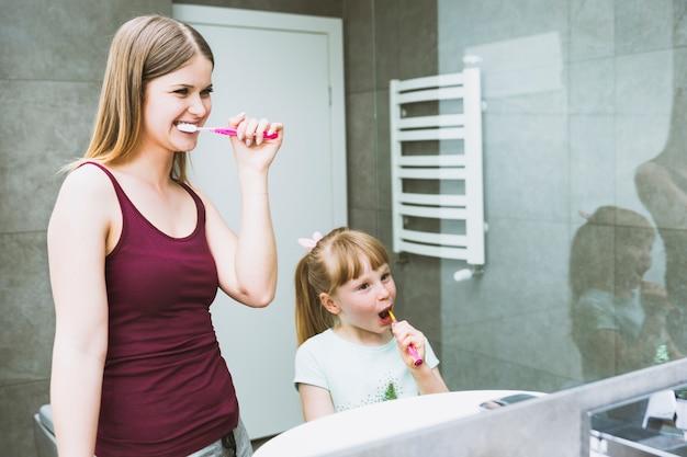 Mulher bonita e menina escovando os dentes