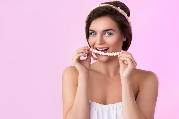 Mulher bonita e miçangas feitas de pequeno marshmallow