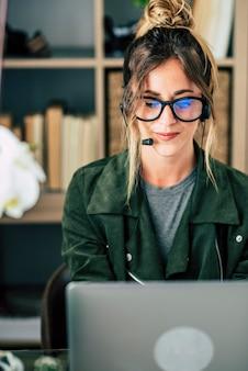 Mulher bonita e moderna trabalhando em casa em videoconferência com laptop e fone de ouvido com microfone