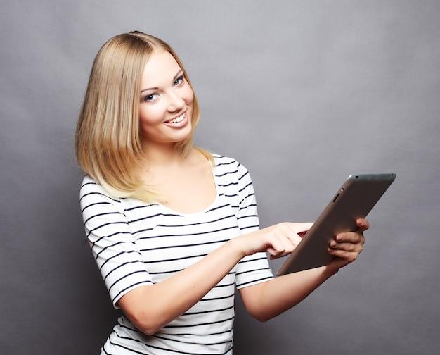 Mulher bonita e moderna usando tablet digital em um espaço cinza