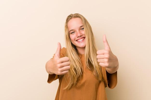 Mulher bonita e natural adolescente com polegares para cima, um brinde por algo, apoio e respeito.
