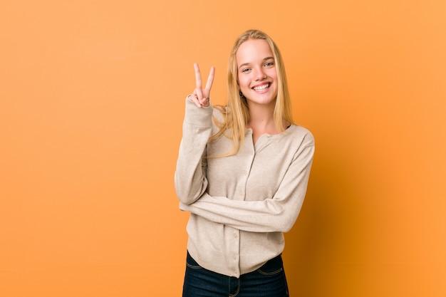 Mulher bonita e natural adolescente mostrando sinal de vitória e sorrindo amplamente