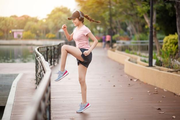 Mulher bonita é ouvir música e exercitar-se no parque