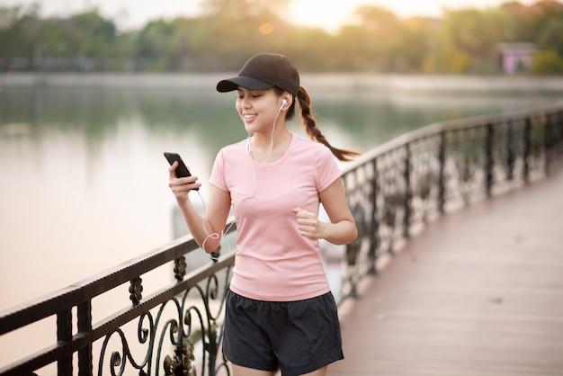 Mulher bonita é ouvir música e fazer jogging no parque
