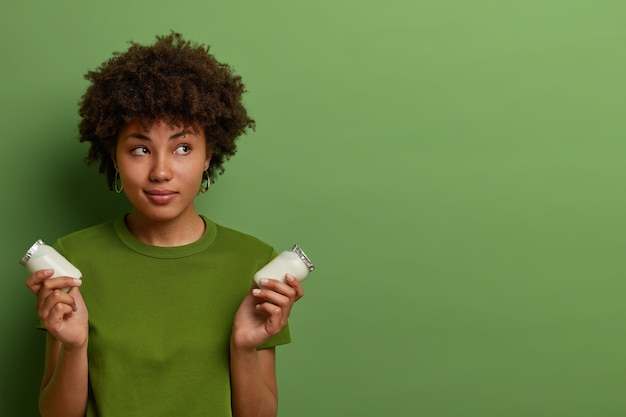 Mulher bonita e pensativa se preocupa com a saúde, segura duas garrafas de vidro de iogurte orgânico fresco nutriente saudável, gosta de comer alimentos lácteos, usa camiseta verde, posa dentro de casa, copie o espaço para a promoção