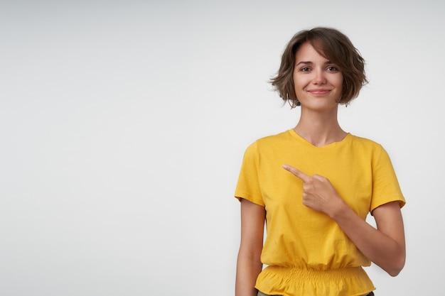 Mulher bonita e positiva com cabelo castanho curto, vestindo roupas casuais enquanto posa, apontando para o lado com o dedo indicador levantado e olhando com um sorriso leve