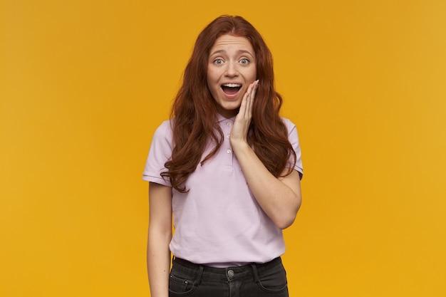 Mulher bonita e positiva com longos cabelos ruivos. vestindo uma camiseta rosa. conceito de pessoas e emoção. tocando sua bochecha. tocado por um elogio. isolado sobre a parede laranja