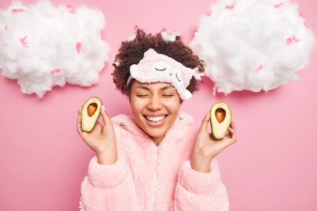 Mulher bonita e positiva segura duas metades de abacate verde fecha os olhos e sorri com os dentes vestidos em pijamas tem penas no cabelo depois de dormir
