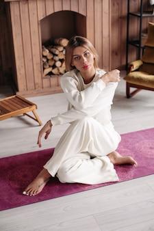 Mulher bonita e relaxada com cabelos claros e roupas brancas se senta no tapete de ioga e olha para o lado