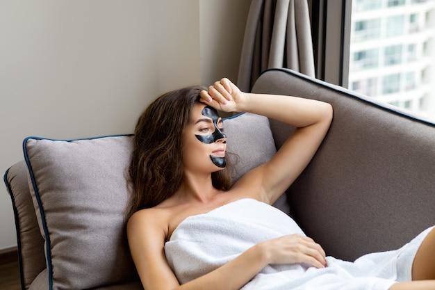 Mulher bonita é relaxante em casa com máscara destacável preta no rosto