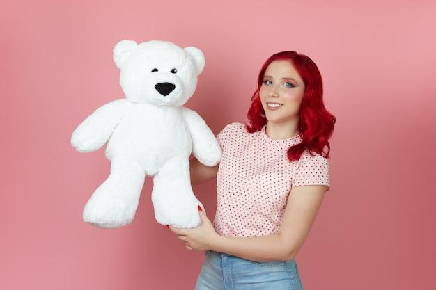 Mulher bonita e romântica com cabelo ruivo acariciando suavemente um grande ursinho de pelúcia branco