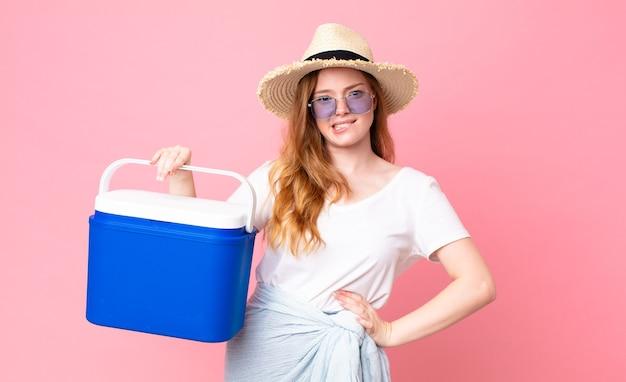 Mulher bonita e ruiva olhando perplexa e confusa e segurando uma geladeira portátil de piquenique