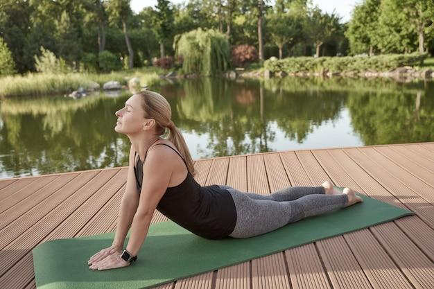 Mulher bonita e saudável em roupas esportivas, mantendo os olhos fechados e praticando ioga em um tapete perto do incrível